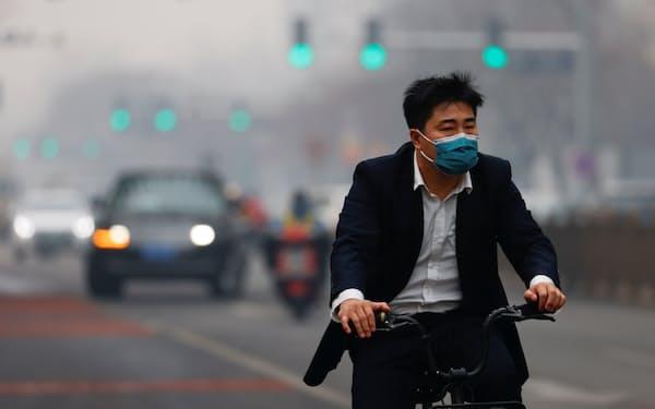 新型コロナウイルスを抑制した中国では再び大気汚染が目立ってきた(2月、北京でマスクをして自転車に乗る男性)=ロイター