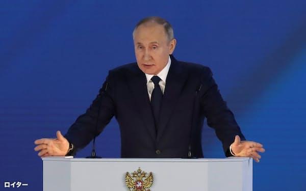 21日、モスクワ市内で年次教書演説を行うプーチン大統領=ロイター
