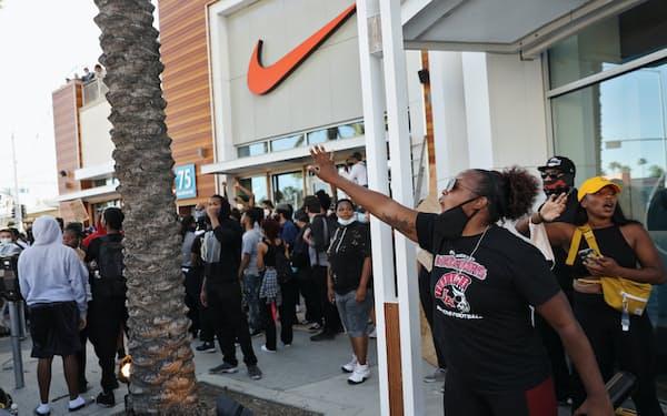 ナイキの店舗を暴徒から守ろうとするデモ参加者ら(20年5月31日、カリフォルニア州)=ロイター