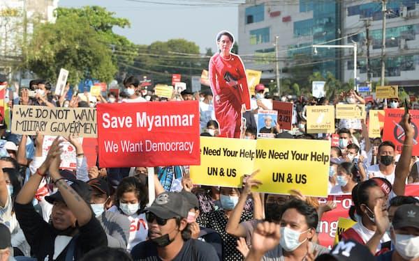 国連や米国に助けを求めるプラカードを掲げた市民(2月、ヤンゴン)=ロイター