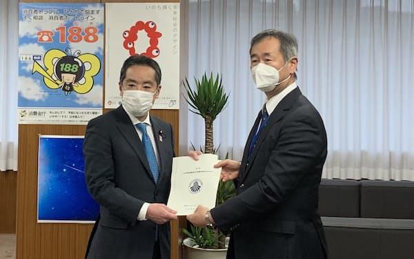 梶田会長(右)から報告書を受け取る井上科技相