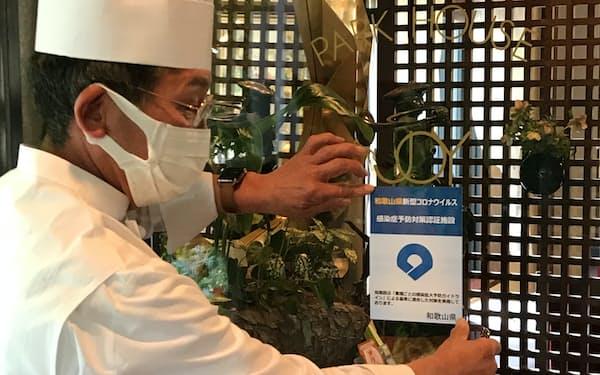 22日、25項目のチェックに合格し、手渡された「認証マーク」をドアに張る「JOY味村」の味村正弘オーナーシェフ(和歌山市)