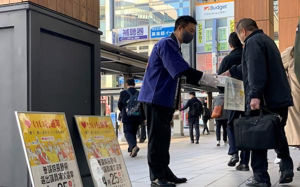 長野県選管は街頭でマスクを配布しながら投票を呼び掛けた(23日、長野駅前)