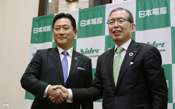 2020年2月、握手を交わす関潤氏(左)と永守重信氏=共同