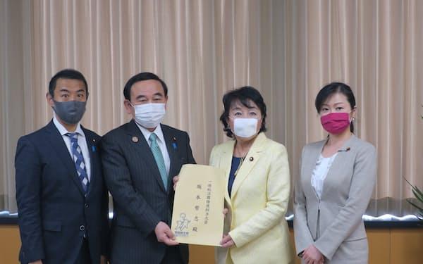 提言を受け取る坂本哲志一億総活躍相(左から2人目。23日、東京・千代田)