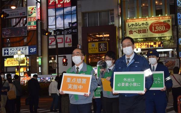 東京・新宿の歌舞伎町周辺で外出自粛を呼びかける都や区の職員ら(12日夜)