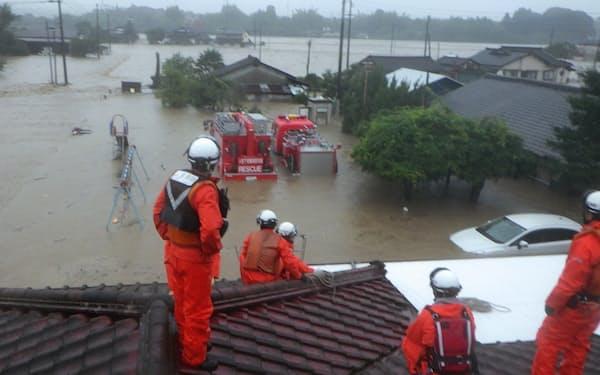増水のため屋根の上に退避する消防隊員