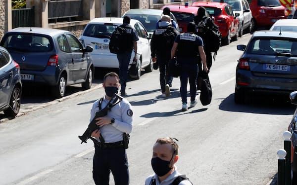 23日、女性刺殺事件の現場を警備する警官ら(パリ郊外)=ロイター