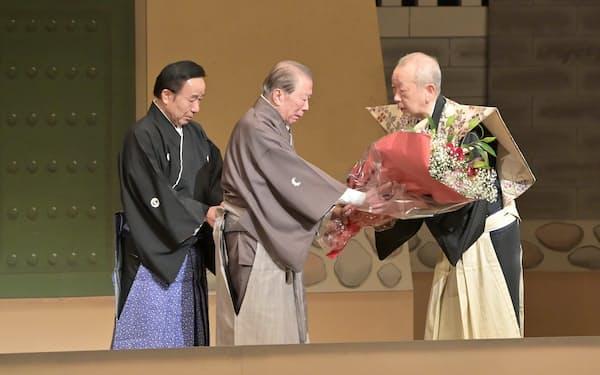 引退公演を終え、三味線の鶴沢清治さん㊨から花束を贈られる吉田簑助さん(24日午後、大阪市中央区の国立文楽劇場)