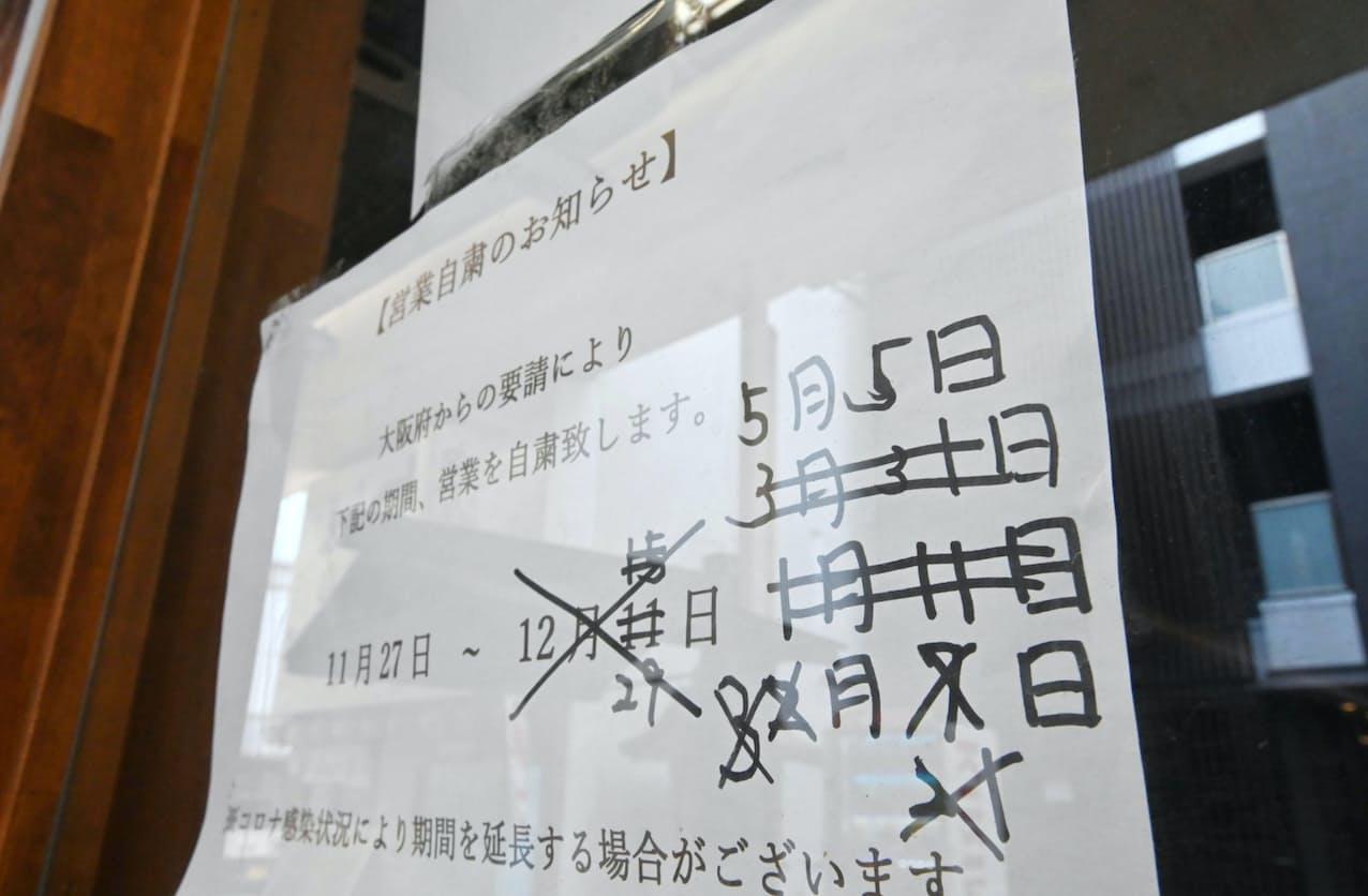 休業期間を何度も書き直した居酒屋の張り紙。5月5日はまん延防止等重点措置の期限(25日午前、大阪市中央区)=柏原敬樹撮影