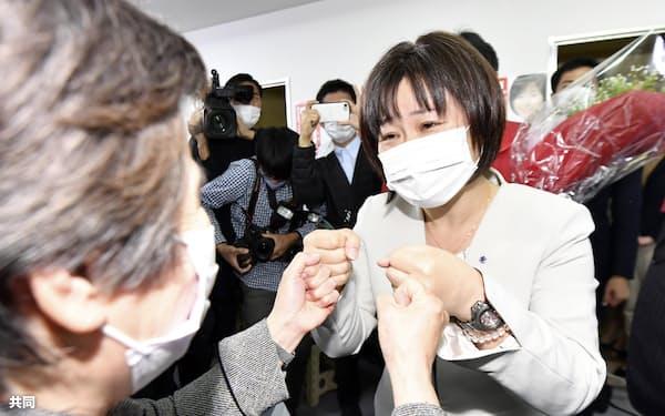 参院広島選挙区再選挙で当選が決まり、支持者とタッチを交わす宮口治子氏(右、25日夜、広島市)=共同