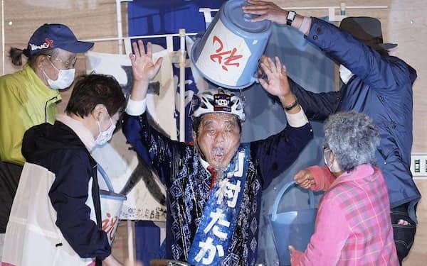 名古屋市長選で5選を決め、支持者から水を掛けられる河村たかし氏(25日夜)=共同