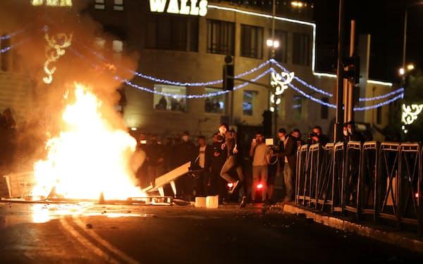 警察との衝突でバリケードを築くパレスチナ人(22日夜、エルサレム)=ロイター