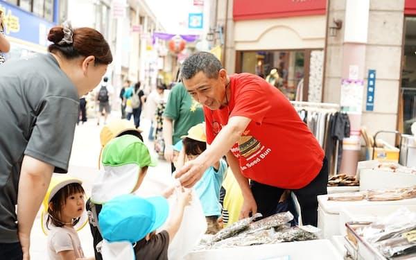 「そらのまちほいくえん」の園児は周辺のお店とも顔なじみ。商店街の雰囲気を変えている(鹿児島市)
