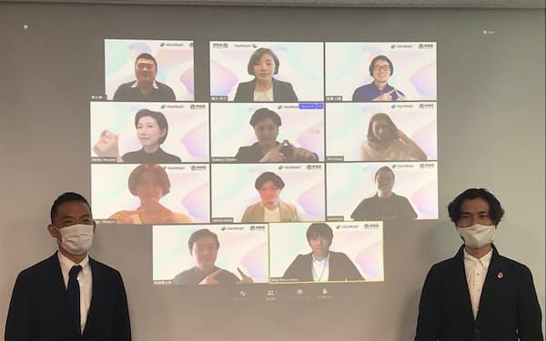 渋谷区の長谷部区長(左)は採用者を映したスクリーンの前で「新しい化学変化を期待したい」と話した(26日)