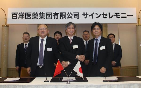 伊藤忠の仲介で契約した(左が百洋医薬グループの付鋼董事長、右がホソカワミクロンの辻本広行執行役員、2019年12月の業務提携時)