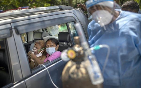インドでは病床や医療用酸素の不足が深刻(24日、車中で酸素吸入を受ける女性)=AP