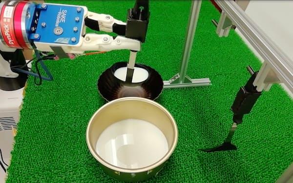 これまでの学習結果から、ロボは牛乳をおたまですくった=早稲田大・尾形所長提供