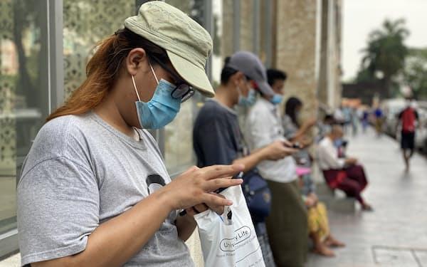 27日、ヤンゴンの商業施設前で館内用のWi-Fiに接続してスマートフォンを操作する男性