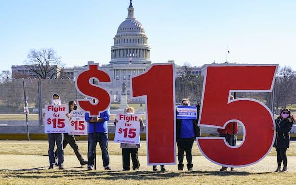 最低賃金を時給15ドルに引き上げるように訴える活動家ら(2月、ワシントン)=AP