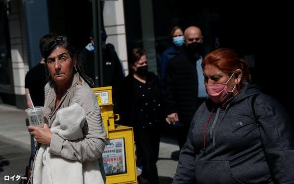 米ニューヨーク市ではマスクを着けずに外出する女性の姿も(27日)=ロイター