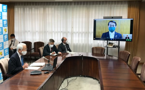 鳥取県の平井知事とオンラインで会談する兵庫県の井戸知事㊧(28日、神戸市)