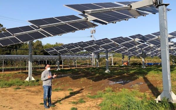 太陽の動きに合わせてパネルが動く発電設備と、ノータスの高橋隆造社長(茨城県行方市)