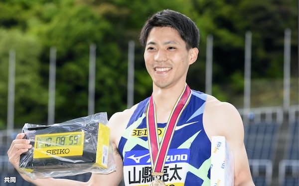 男子100メートルで優勝し、表彰式で笑顔を見せる山県=共同