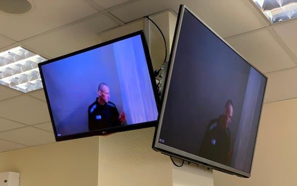 裁判所のテレビ画面に映った収監中のナワリヌイ氏(29日、モスクワ)=ロイター