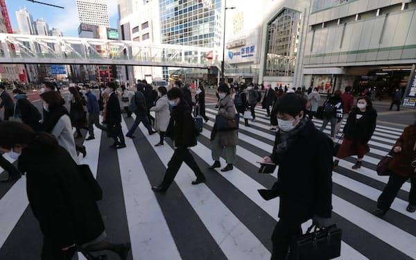 緊急事態宣言が発令された後、マスク姿で通勤する人が行き交う新宿駅前(2021年1月)