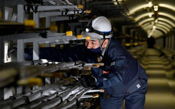 通信ケーブルを敷くトンネル「とう道」で専用の道具を使い壁の状態を調べる宮地さん=笹津敏暉撮影