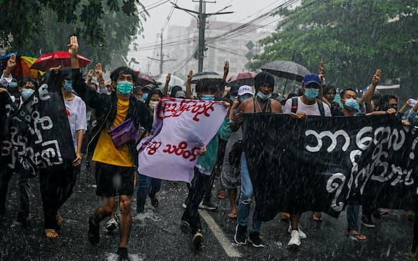 4月30日、ヤンゴンで大雨のなかフラッシュモブの抗議デモを行う若者ら