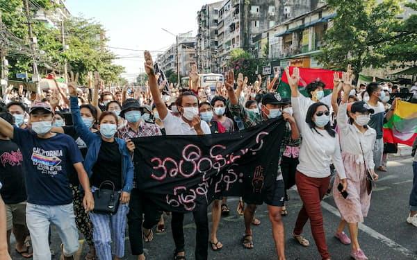 2日、ヤンゴンで民主化を求めてデモ行進する人々