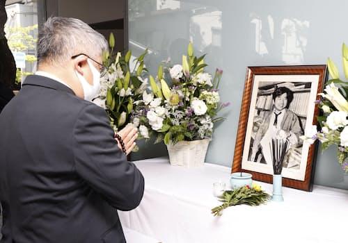 朝日新聞阪神支局に飾られた小尻知博記者の遺影の前で、手を合わせる男性(3日、兵庫県西宮市)=共同