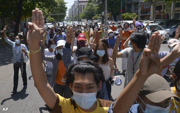 4日、ヤンゴンで国軍への抵抗を示す3本指をあげて抗議デモを行う人々                                                         =AP
