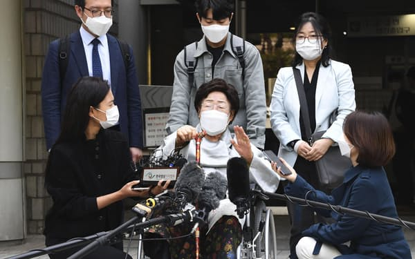 4月21日、ソウル中央地裁での判決後、記者団の取材に応じる元従軍慰安婦の李容洙さん(手前中央)=共同