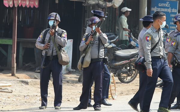 デモ隊が行進するなか、武器を構えるミャンマー警察=ロイター