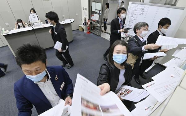 上場企業の2020年9月中間決算発表がピークを迎え、報道機関向けに資料を投函する企業関係者=30日午後、東京・日本橋兜町の東京証券取引所