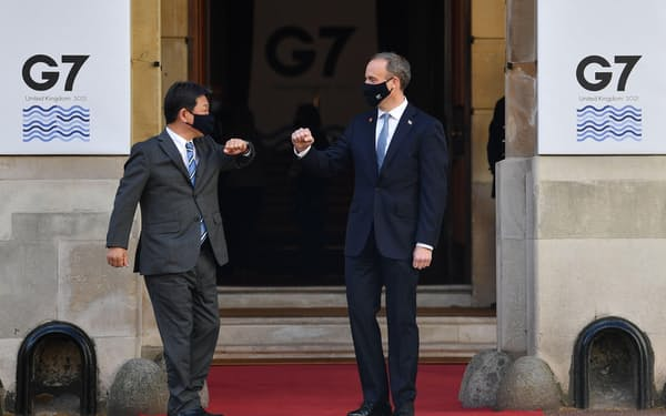 G7外相会合で、ラーブ英外相(右)に出迎えられる茂木外相=5日、ロンドン(ロイター=共同)