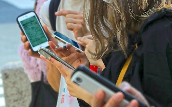 スマートフォンを片時も手放さない若者たち(東京・渋谷)