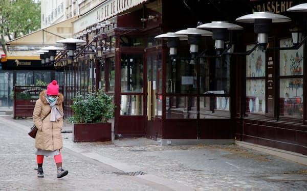 閉鎖されたレストランの前を歩くマスク姿の女性(6日、パリ)=ロイター