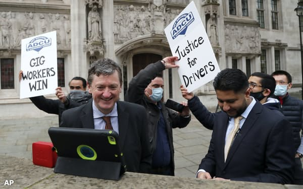 英最高裁の判決を受けて喜ぶウーバーの運転手(2月、ロンドン)=AP