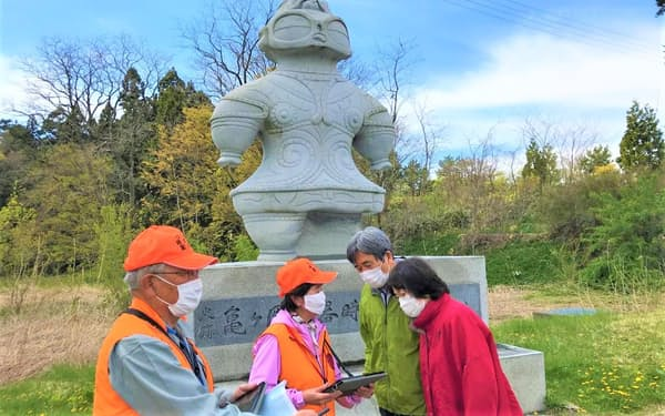 亀ケ岡石器時代遺跡でタブレットを使って説明するガイドの新岡絹子さん=左から2番目(5月2日、青森県つがる市)