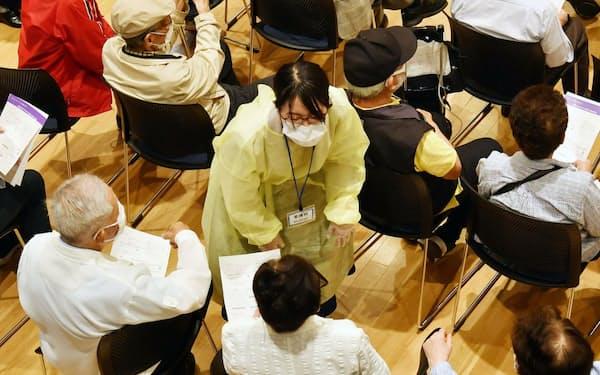 新型コロナウイルスワクチンの集団接種会場で経過観察中の高齢者に話しかける看護師(10日午後、神戸市兵庫区)
