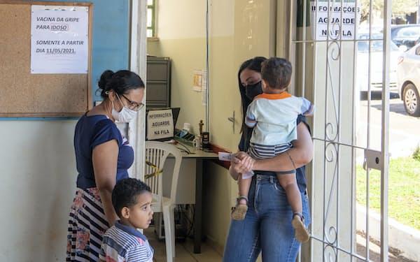 マスクを着け、インフルエンザのワクチン接種を待つ市民(3日、サンパウロ州セハナ)