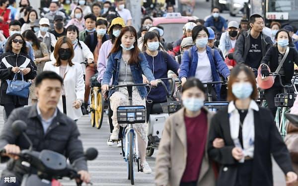北京市内の交差点を行き交う市民たち(10日)=共同