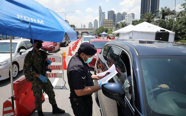 新型コロナ抑制のための活動制限下で、検問にあたる警察官(10日、クアラルンプール近郊)=ロイター