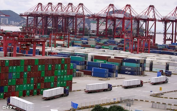 FILE PHOTO: Containers and lorries are seen at the Yangshan Deep Water Port in Shanghai, China, as the coronavirus disease (COVID-19) outbreak continues, October 19, 2020. REUTERS/Aly Song/File Photo