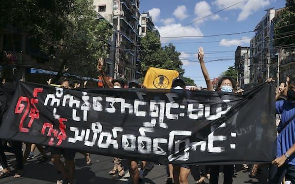 11日、ヤンゴンで抗議デモを行う人々=AP