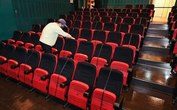 映画館「ポレポレ東中野」では上映前に新型コロナウイルス対策として1席ずつ空けられた座席の消毒作業を行っている(11日、東京都中野区)